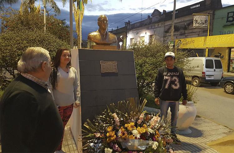 (Dos de los integrantes de la juventud de Somos Rodríguez colocando la ofrenda floral)